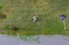 Top view of a city landscaper cutting grass with lawn mower;. Top view of a city landscaper  cutting grass with lawn mower Royalty Free Stock Photo