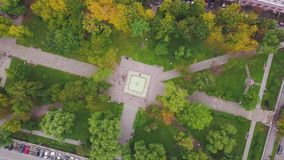 Top view of city park. Clip. Small park in city center with number of cars standing in parking lot. Ecological park in. City in autumn stock video