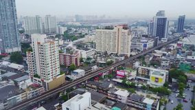 Top view city and Sky Train of Bangkok going out from station. Top view of modern city and traine going.  stock video
