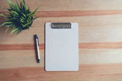 Top view clipboard with pen and white paper on the table background. stock images