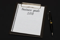 Top view of clipboard and white sheet written with Business goal. S 2018 on black background. Business Concept Royalty Free Stock Images