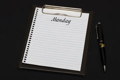 Top view of clipboard and white sheet written with Monday on black background. Business Concept stock photos