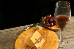 Rare, wood, round plate of wedge of cheese, knife and glass of red wine. Top view, close distance of a rare, wood, round plate of wedge of cheese, cheese knife royalty free stock photography