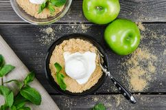 Top view close up Apple crumble dessert with vanilla ice cream, green mint on grey wooden table background. fork in cake. Top view close up Apple crumble dessert Stock Photography