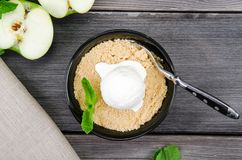 Top view close up Apple crumble dessert with vanilla ice cream, green mint on grey wooden table background. fork in cake. Top view close up Apple crumble dessert Royalty Free Stock Photo