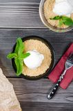 Top view close up Apple crumble dessert with vanilla ice cream, green mint on grey wooden table. fork with cake on paper. Top view close up Apple crumble dessert Stock Photo