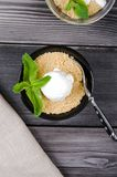 Top view close up Apple crumble dessert with vanilla ice cream, green mint on grey wooden table. fork with cake on. Top view close up Apple crumble dessert with Stock Images