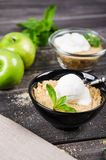 Top view close up Apple crumble dessert with vanilla ice cream, green mint on grey wooden table. fork with cake on. Top view close up Apple crumble dessert with Royalty Free Stock Photos