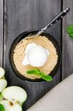 Top view close up Apple crumble dessert with vanilla ice cream, green mint on grey wooden table. fork with cake on. Top view close up Apple crumble dessert with Royalty Free Stock Photography