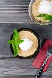 Top view close up Apple crumble dessert with vanilla ice cream, green mint on grey wooden table. fork with cake on paper. Top view close up Apple crumble dessert Stock Photos