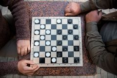 Mature male friends playing draughts outdoor Royalty Free Stock Photography