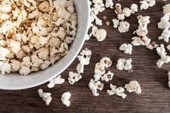 Directly above close-up of bowl filled with popcorn on rustic wooden table. Top view close-up of bowl filled with popcorn on rustic wooden table Stock Photo