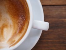 Top view and close up coffee in white cup on wooden table. royalty free stock photography