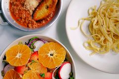 Top view and close up dinner table, salad and Fettuccine Bolognese placed on white dish and a white table. Top view and close up dinner table, Italian cuisine royalty free stock photography