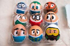 Top view. Close up. Easter eggs painted as faces with medical masks, respirators. Easter during coronavirus