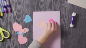 Girl`s hands glueing a card. Valentine`s Day stock video