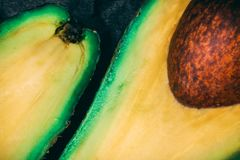 Top view close up of a half ripe avocado on smooth black surface. stock images