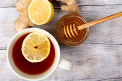 Top view. Close up. Healthy concept. Tea, lemon, ginger, honey on a white wooden background. Flat lay. Treatment of cold stock photo