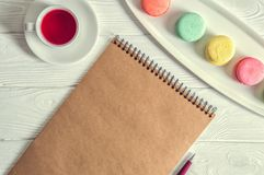 Top view. Close up, macro. Provence morning. Colorful french macarons, brown vintage blank, a pen, a cup of berry tea. Copy space royalty free stock photo