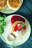 Top view. Close up, macro. Rustic breakfast. Cheese pancakes, poured with cream and decorated with strawberries. Wooden background stock image