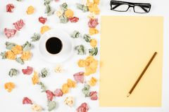 Messy white table with supplies. Top view and close up of messy white office table with various colorful supplies and coffee cup Royalty Free Stock Photography