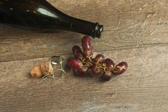 Top view, close up of an open bottle of vintage, french, champaign. A champaign cork with the wire retaining cap and a bunch of red, ripe grapes on a wood royalty free stock images