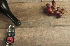 Top view, close up of an open bottle of vintage, french, champaign. A champaign stopper and a bunch of red, ripe grapes on a wood table top royalty free stock photo