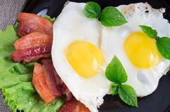 Top view close-up on a plate with fried eggs and fried bacon Royalty Free Stock Image