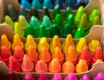 Colorful crayons in small boxes stock photography