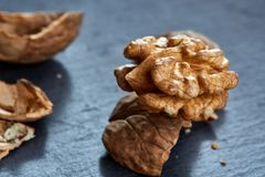 Top view close-up shot of cracked walnuts on dark background, shallow depth of field, macro. Soft blurred, some copy space for your text. Healthful and royalty free stock photos