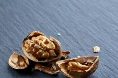 Top view close-up shot of cracked walnuts on dark background, shallow depth of field, macro. Soft blurred, some copy space for your text. Healthful and stock photos