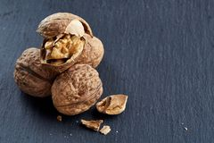 Top view close-up shot of cracked walnuts on dark background, shallow depth of field, macro. Soft blurred, some copy space for your text. Healthful and royalty free stock images