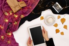 Top view,close-up of tablet computer with blank screen in hands of woman dressed in knitted sweater. Nearby is cup of Royalty Free Stock Images