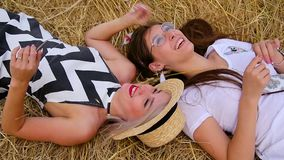 Top view of close-up of two cute positive girls the blonde and the brunette fool around and laugh lying on golde. Top view of close-up of two cute positive girls stock video footage