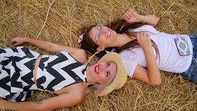 Top view of close-up of two cute positive girls the blonde and the brunette fool around and laugh lying on golde. Top view of close-up of two cute positive girls stock footage