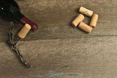 Top view of an un open bottle of vintage, french , red wine. Top view, close up of an unopen bottle of vintage, french, red wine, a corkscrew with attached cork stock images