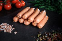 Top view closeup heap of sausages with rucola and tomatoes. Top view closeup heap of raw long thick sausages with pink salt, spices, rucola and tomatoes cherry stock image