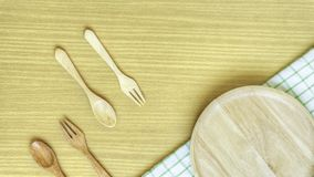 Top view closeup set of wooden cutlery utensil. Wooden fork, spoon, plate on wooden table background. Clean green and white checke royalty free stock photos