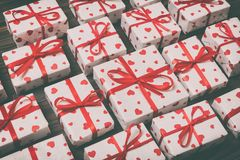 Top view closeup wrapped valentine or other holiday handmade present in paper with red ribbon and heart. Present box, decoration. Of gift on wooden table. Toned stock image