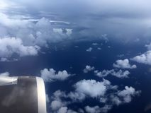 The top view of clouds and sky from an airplane window.  Stock Photography