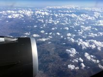 The top view of clouds and sky from an airplane window.  Stock Photo