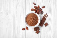Top view of cocoa powder and beans with broken chocolate bar on white wooden background