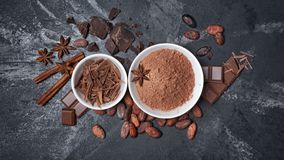 Top view of cocoa powder and chocolate chips in white bowls and whole cocoa beans with spices