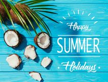 Top view of coconuts and green palm leaves on turquoise wooden surface with happy summer. Holidays lettering royalty free stock photography