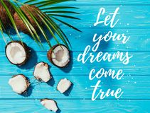 Top view of coconuts and green palm leaves on turquoise wooden surface with let your dreams come. True lettering royalty free stock images