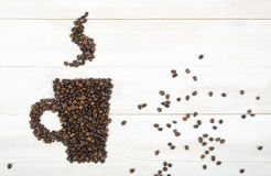 Top view coffee beans making a shape of cup on wooden surface Stock Photos