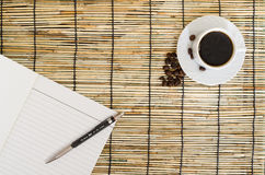 Top view of Coffee beans with white cup, blank notebook and pen on mat Royalty Free Stock Images