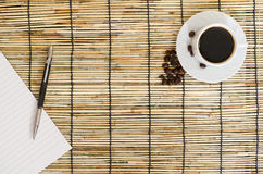 Top view of Coffee beans with white cup, blank notebook and pen on mat. Coffee beans with white cup, blank notebook and pen on mat royalty free stock photo