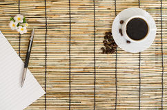 Top view of coffee beans with white cup on japan mat Royalty Free Stock Photos