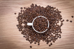TOP VIEW: Coffee beans in a white cup and on the table. Stock Photography